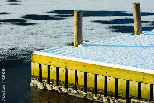 Snow covered corner of a wooden pier in frozen water.