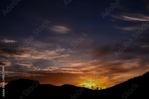 Foto Murales Sun behind a Mountain Silhouette