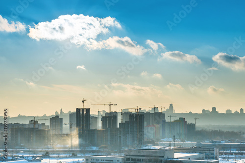 Landscape sunset in the city with blue sky, sun and industrial cranes
