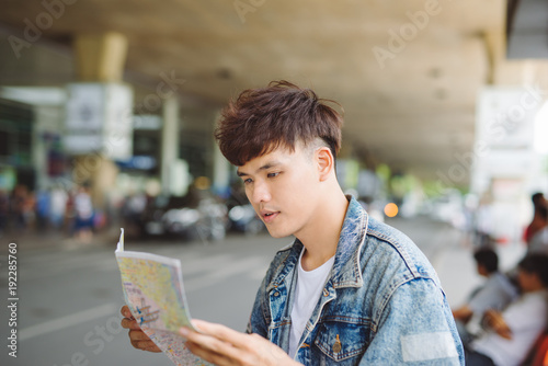 Asian male tourist reading map while waiting for taxi at the airport