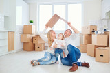 A happy family moves to a new apartment. Mother, father and child with boxes in the room of the new house. - 192286527