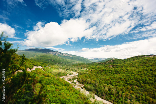 Fotobehang Lente Scenic mountain landscape with green hills and the river between the mountains, blue sky with clouds. The Caucasus Mountains, Georgia, Europe. Nature and travel background.