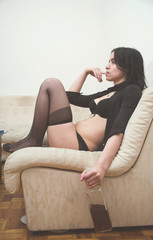 Sexy girl sitting on sofa in apartment and holding bottle of whiskey