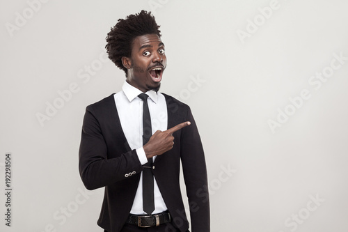 African businessman pointing finger at copy space . Studio shot, gray background