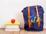 Blauer Schulrucksack, ein Stapel Bücher und ein roter Apfel auf einem braunen Holzfußboden. Bildung, Schule, Wissen. - 192300519