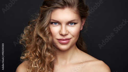 Beautiful female with curly hairstyle posing in studio. Portrait of pretty young model with waved hair over black background.
