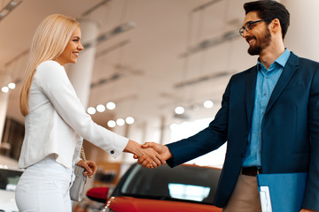 Young woman shaking hands after a successful car buying with the seller