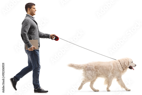Man with a book walking a dog