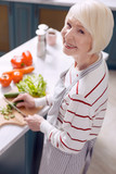 I love cooking. Upbeat elderly woman in an apron posing for the camera and smiling cheerfully while cutting cucumbers and making a salad - 192307383