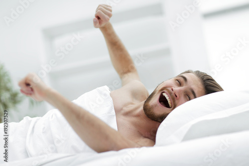 happy man waking up in a comfortable room