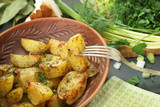 Baked with spices potatoes in a rustic style on a plate surrounded by greenery, one slice is pinned on the fork, before eating - 192307736