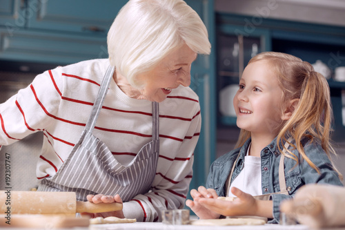 Sharing vital tips. Adorable little girl helping her grandmother make cookies and chatting with her, discussing the process, while the woman sharing her experience and rolling out dough