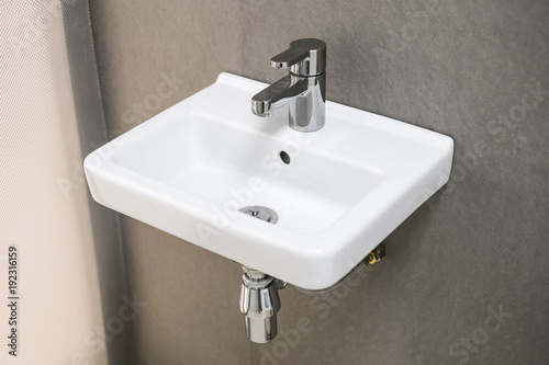 White small low-cost washbasin in small apartment, Washbasin with mixer, Ceramic sink
