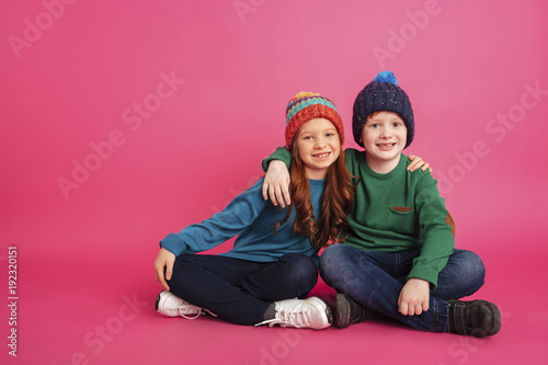 Leinwandbild Motiv Cheerful brother and sister hugging and looking camera