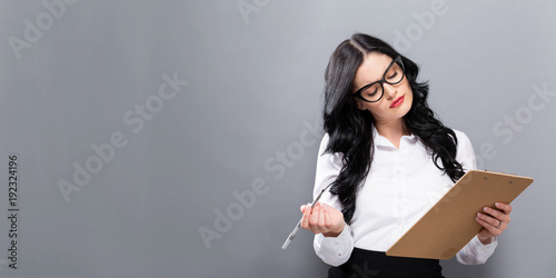 Office woman with a clipboard on a solid background