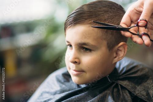The boy getting haircut by scissor in barbershop. Barber use scissor