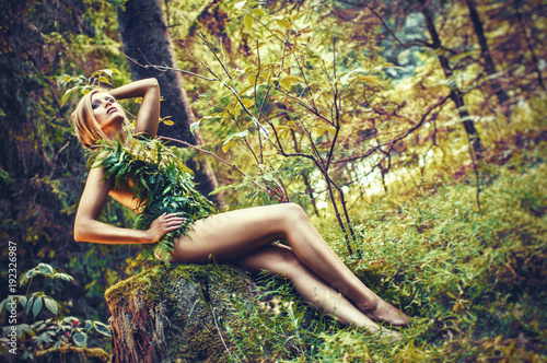 beautiful blonde woman with leaves dress in nature, glamour and fashion photography in summer