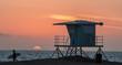 Surfer running past lifeguard tower at sunset on Huntington beach in southern California
