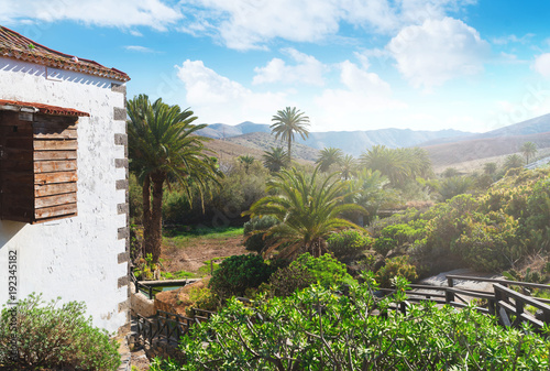 Fotobehang Canarische Eilanden corner of old traditional house in historic village of Betancuria on Fuerteventura island with lush green vegetation and mountain range in background on sunny day