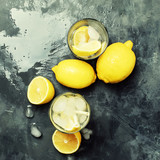 Summer refreshing lemonade with ice and soda, gray background, top view