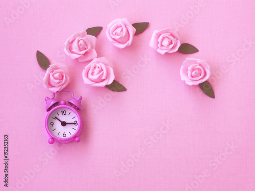 Plagát pink paper texture background with alarm clock, rose flowers