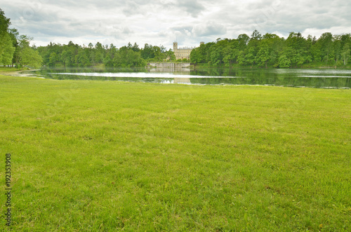 Foto op Canvas Pistache Green meadow on the banks of the lake.