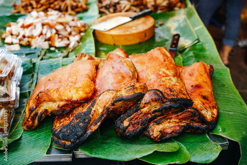 large fried pieces of meat on a banana leaf. Asian street food trade. Street food. © galaganov