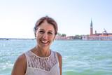 Lächelnde Touristin am Ufer in Venedig, im Hintergrund San Giorgio Maggiore - 192389328