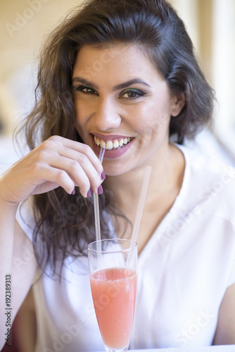 Keuken foto achterwand Sap Young beautiful woman drinking a grapefruit juice using a straw, sitting in a well lit cafe