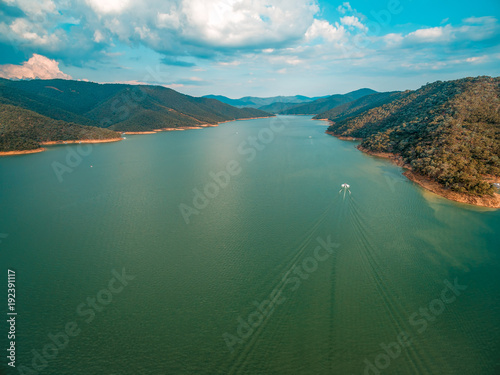 Fotobehang Groen blauw Aerial landscape of boat sailing in Lake Eildon at sunset in Australia