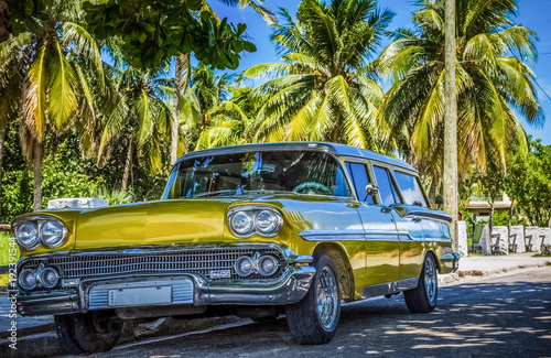Złote amerykańskie klasyczne parkingi pod błękitne niebo i palmy w Varadero Kuba - seria reportaż Kuba