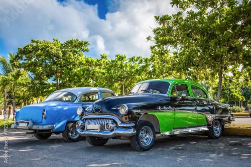 Dwa amerykańskie samochody klasyczne parku pod błękitne niebo w Varadero Kuba - HDR - Serie Kuba reportaż