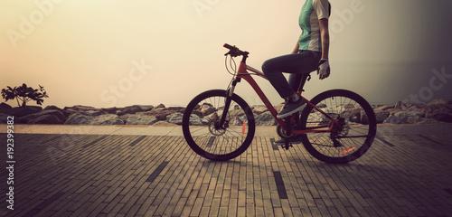 cyclist riding bike on the sunrise coast path