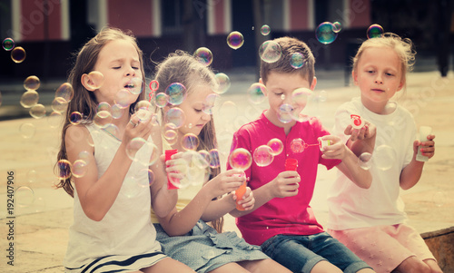 Four kids blowing soap bubbles