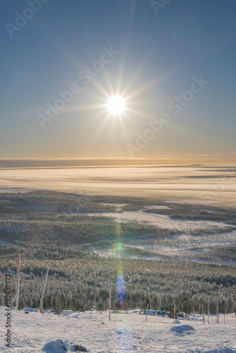 Foto Murales Sunshine and halo effect at blue sky in Lapland Finland