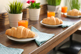 Plates with delicious croissants and glasses of juice on wooden table in cafe - 192420102