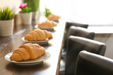 Plates with delicious croissants on wooden table in cafe - 192420104