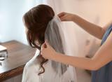 Hairdresser preparing bride before her wedding in room - 192420502