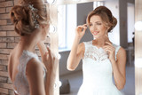 Beautiful young bride in white wedding dress with makeup created by professional artist near mirror indoors - 192420503