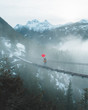 Red Umbrella on Misty Suspension Bridge in Mountains