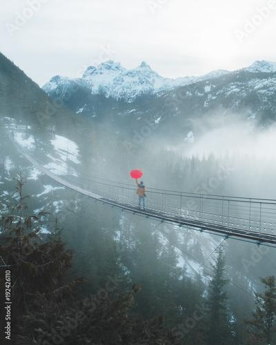 Foto op Plexiglas Canada Red Umbrella on Misty Suspension Bridge in Mountains
