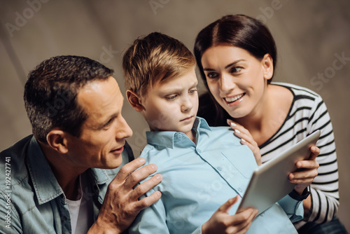 Persuasive strategies. Gentle young parents surrounding their pre-teen son and touching him tenderly while persuading him to stop binge-playing on tablet