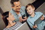 Pleasant discussion. Upbeat young family talking to each other while sitting on the sofa and using their phones - 192427933