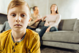All alone. The focus being on the upset little boy feeling lonely and looking sadly at the camera while his parents sitting on the couch and quarrelling in the background - 192428379