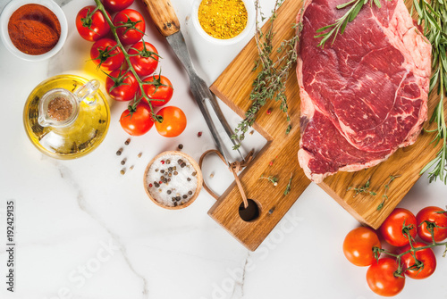Foto op Canvas Steakhouse Fresh raw meat, lamb beef marble steak on a cutting board, with ingredients for cooking. On white marble table, copy space top view
