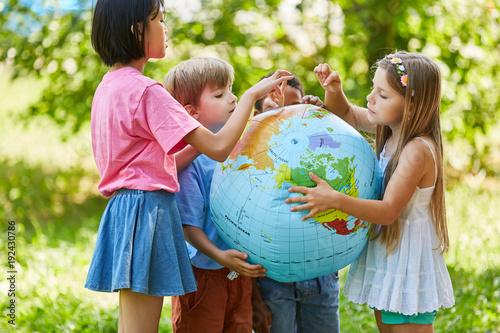 Fototapeta Kinder halten zusammen eine Weltkugel