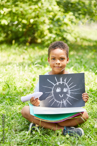 Foto Murales Afrikanischer Junge zeigt Kreide Bild einer Sonne