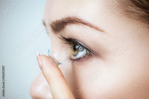 Close-up shot of young woman wearing contact lens.