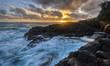 Dramatic sunrise illuminates a dual waterfall near Kauai's infamous Queen's Bath.