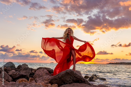 beautiful-young-sexy-blonde-posing-in-evening-red-dress-on-sea-quay-on-the-sunset